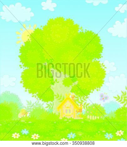 Small Wooden House From A Fairytale With Decorations, A Porch And A Fence Under A Big Branchy Tree O