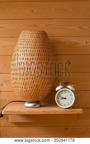 Bedroom Interior Detail, Wooden Panelling, White Clock, Braided Lampshade. Warm Home Mood.