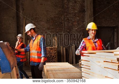 Young Workers Working In Wood Factory Manufacturing. Workers Wears Protected Helmet, Gloves And Clot