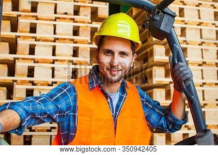 Workman Wears Protective Helmet, Vest And Gloves. Worker Standing Near Forklift In Warehouse.