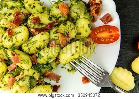 Homemade Gnocchi With Spinach And Prosciutto On Black Slate Board.  Traditional Italian Food. Potato