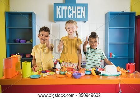 Three Kids Giving Thumbs Up At Toy Kitchen. Little Girl And Two Boys In Kids Playroom. Kids Leisure
