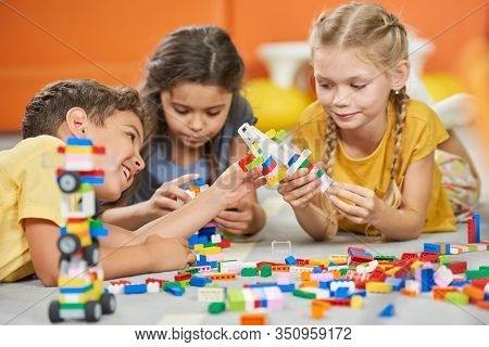Group Of Kids Playing With Plastic Blocks. Children Playing With Constructor. Developing Toys For Ki