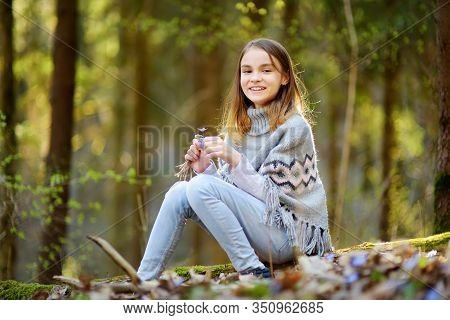 Adorable Young Girl Picking The First Flowers Of Spring In The Woods On Beautiful Sunny Spring Day.