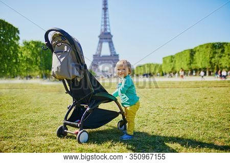 Adorable Happy Baby Girl Standing Next To Her Pushchair In Paris Near The Eiffel Tower. Smiling Todd