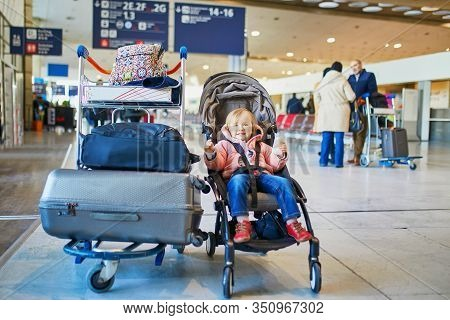 Adorable Little Toddler Girl In International Airport. Small Child Sitting In Pushchair Near Heavy L