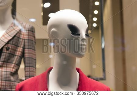 Bald White Mannequin With Large Glued Eyelashes In A Red Jacket. In The Background Is Another Manneq