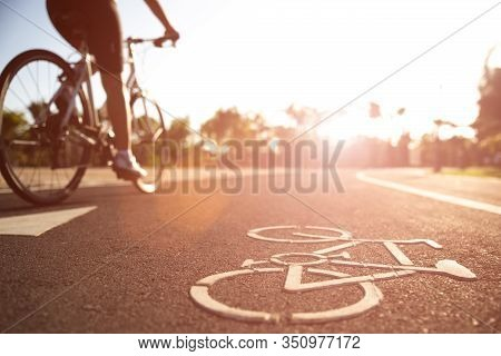 Close Up Cycling Logo Image On Road With Athletic Women Cyclist Legs Riding Mountain Bike In Backgro