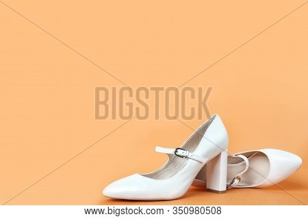 White High Heel Women's Shoes On A Orange Background. Side View, Close Up.