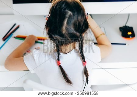 Rear View Of Beautiful Kid Girl With Two Braids, Drawing With Pencils At Home Next To The Computer.
