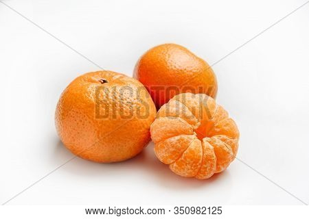 Tangerines On A White Background. One Peeled Tangerine Lies Next To Two Tangerines In A Peel.