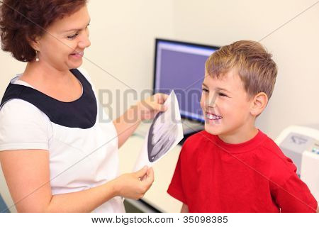Dentist holds jaw x-ray image for happy boy in dental clinic