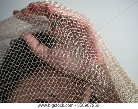 Women Covering Their Faces With A Cloth,imprisoned The Fabric Is White Mesh.