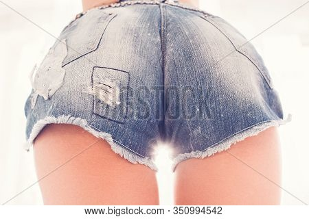Provocative Woman. Female Buttocks. Frayed Denim Shorts.