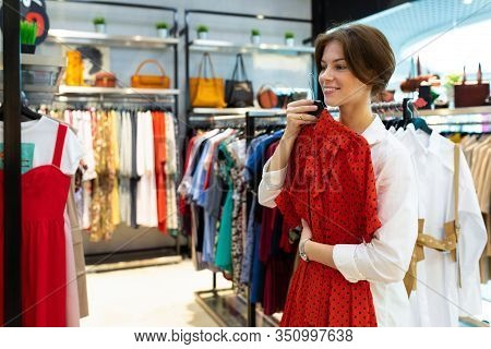 Smiling Attractive Young Woman Chose A Red Dress For Discount Shopping In A Fashion Boutique.