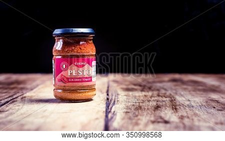 Perth, Scotland - 11 November 2019: Pesto Made Of Sundried Tomatoes Isolated On Vintage Wooden Board