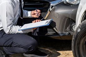 Insurance Agent Inspecting Assessed Damaged Car Checking And Signing On Report Insurance Claim Form