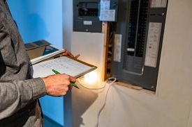 Home Inspector In Front Of Electric Distribution Board During Inspection, Selective Focus And Close