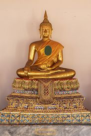 Golden Buddha Statue  On White Wall At Bangkok,thailand