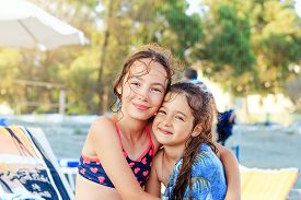 Two Cute Little Girls Hugging And Smiling At The Seaside At  Summer Sunny Day, Ocean Coast, Happy Ki