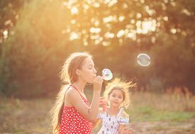 Two Cute Little Girls Blowing Soap Bubbles Outdoor At Summer Day - Happy Childhood