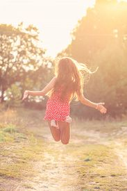 Portrait Of Beautiful Teenager Girl  Is Jumping Outside At  Summer Sunset