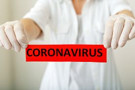 Coronavirus, Red Warning Sign With The Text Coronavirus In Doctor Hands In White Coat And Gloves. Ep