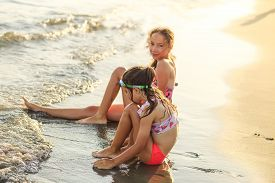 Two Cute Little Girls Sitting At The Sea And Playing With Waves  At Sunset.  Summer Sunny Day, Ocean