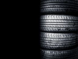 Studio Shot Of A Set Of Summer Car Tires Isolated On Black Background. Tire Stack Background.