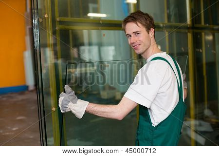 Worker in glazier's workshop warehouse or storage handling glass poster