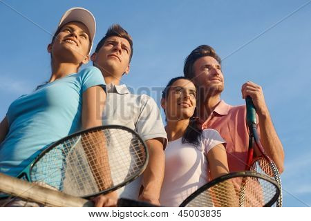 Team of smiling tennis players, photographed from below.