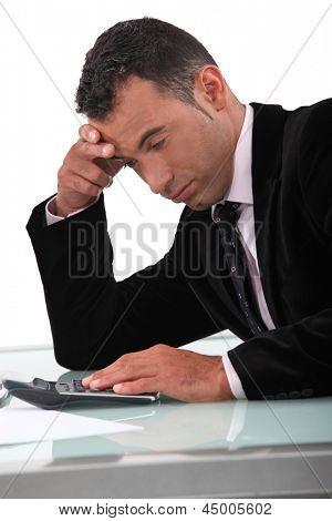 Jaded man using a calculator
