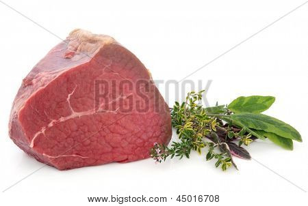 Fillet of beef meat joint with fresh herb sprigs over white background.