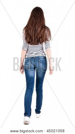 back view walking woman in jeans. beautiful brunette girl in motion. backside view person. Rear view people collection. Isolated over white background. The girl in striped T-shirt  goes ahead