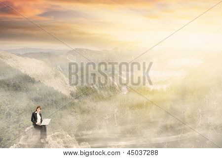 Business woman working at dream with beautiful misty mountain landscape under dramatic sunlight. Photo compilation concept about business, dream, freedom, relax, comfortable etc.