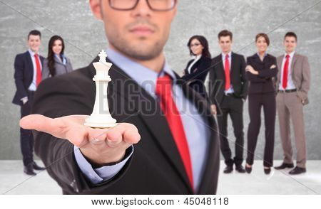 young business man leader of a successful business team holding the white king of chess on the top of his hand