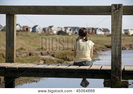 Girl Sitting On Bridge