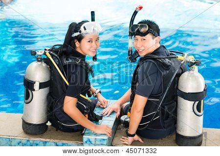 Asian people at the diver Course in diving school in wetsuit with an oxygen tank