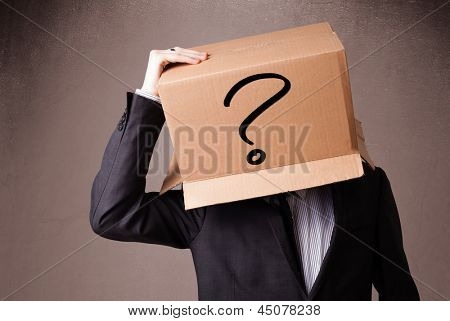 Businessman standing and gesturing with a cardboard box on his head with question mark poster