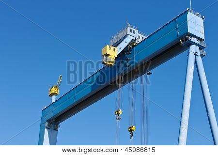 Gantry Crane At Shipyard On The Background Of Blue Sky