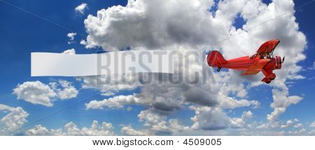 Vintage red airplane with blank banner over a bright sky with clouds poster