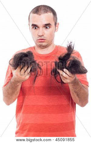 Shocked bald man holding his long shaved hair isolated on white background poster