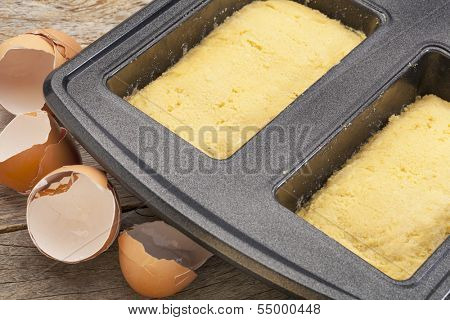 dough for coconut flout gluten bread in a baking pan with broken egg shells