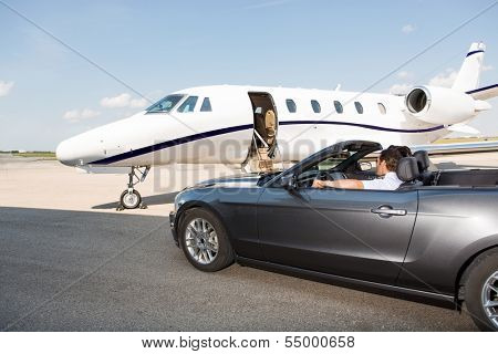 Pilot in convertible parked against private jet at airport terminal