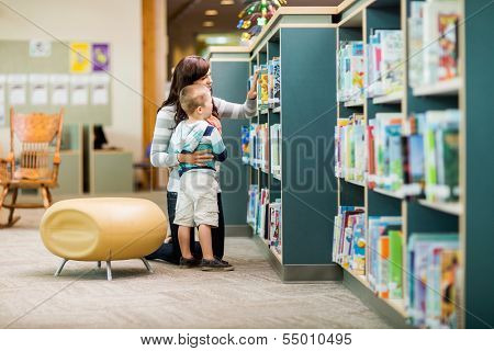 Full length of teacher and boy selecting book from bookshelf in library