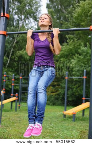 Young beautiful girl doing exercise on a horizontal bar on the outdoor sports ground