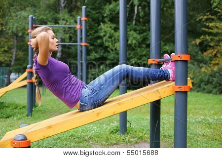 A young girl doing abdominal crunches on the outdoor sports ground