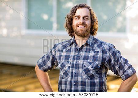 Portrait of confident mid adult carpenter standing at construction site