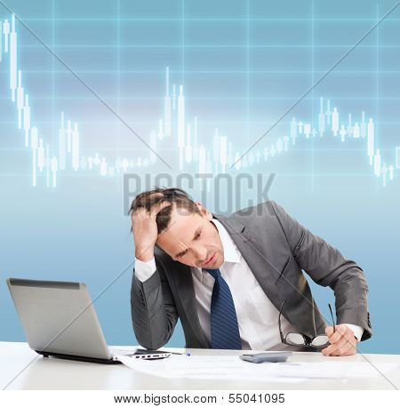 business, office and money concept - stressed businessman in black eyelgasses with laptop computer, papers, calculator and forex chart poster