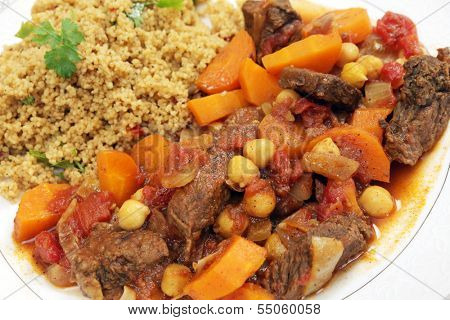 Plate of traditional Moroccan beef tagine with couscous, garnished with flat-leaf parsley